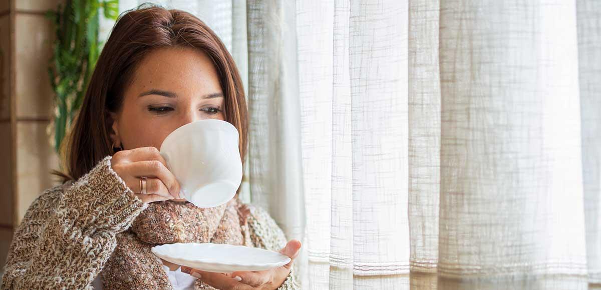mujer bebiendo una infusión al lado de la ventana