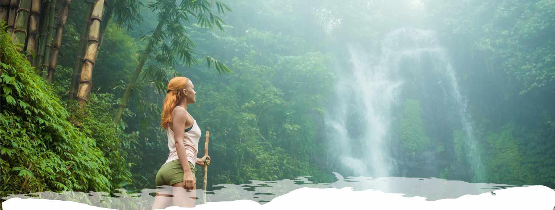 Mujer en medio de un bosque de bambú mirando una cascada