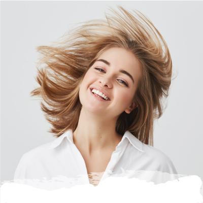 Chica sonriente agitando la cabeza con el pelo al viento